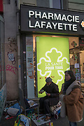 """March, 23rd 2020 - Paris, Ile-de-France, France: Homeless near a pharmacy during the spread of the Coronavirus, during the eigth day of near total lockdown imposed in France. A week after President of France, Emmanuel Macron, said the citizens must stay at home from midday on Tuesday for at least 15 days. He said """"We are at war, a public health war, certainly but we are at war, against an invisible and elusive enemy"""". All journeys outside the home unless justified for essential professional or health reasons are outlawed. Anyone flouting the new regulations is fined. Nigel Dickinson"""