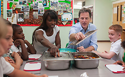 ***EMBARGO 12.01AM Tuesday 17 June.*** © Licensed to London News Pictures. 12/06/2014. Wallington, UK. Lorraine Pascale and Nick Clegg make a fruit salad with the schoolchildren.  Ahead of an announcement on new food standards for schools, Deputy Prime Minister Nick Clegg and celebrity chef Lorraine Pascale visit Foresters Primary School where they picked fruit with schoolchildren from the school's vegetable patch, prepared a fruit salad, helped the school chefs to serve food and sat with the children as they ate lunch. Photo credit : Stephen Simpson/LNP