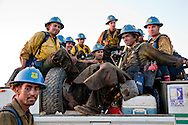 The Texas Canyon Hotshots hitch a ride from the fire line to their trucks during the evening shift change at the La Brea Fire.