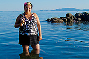 Woman with small dog (boston terrier mix) standing in shallow water on lake