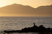 A fisherman is silhouetted in front of the mountains on the south of the island in Puerto del Carmen, Lanzarote, Spain on 21st November 2020. Beaches and resorts across the island are nearly deserted since tourism plummeted due to Covid restrictions elsewhere in Europe. Although the Canary Islands have been relatively unscathed by the virus, with 155 lives lost from 2.1 million residents, the region is heavily dependent on tourism and locals are hoping that numbers recover as lockdown measures ease and vaccines potentially reduce the numbers of infections.