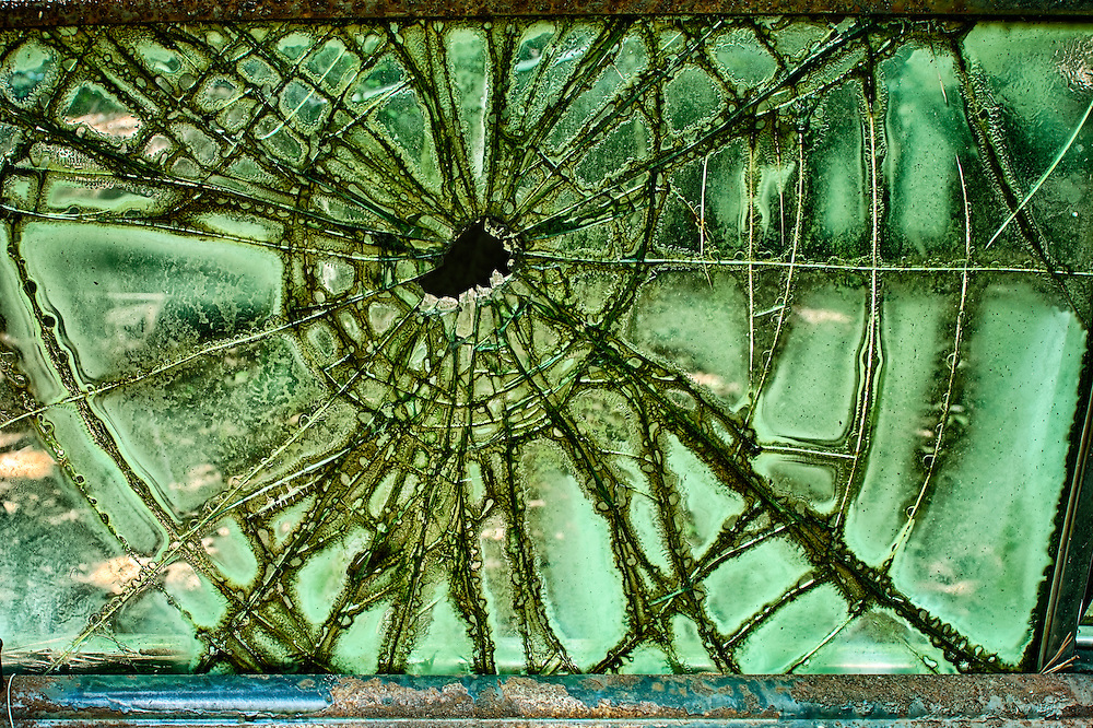 A broken, shattered window on an antique car in the Old Car City junkyard in Georgia glows through a spiderweb pattern of cracks radiating from the point of impact.
