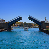 """""""Through the Drawbridge""""<br /> <br /> Watching a boat pass through the drawbridge in Charlevoix Michigan on a beautiful day!"""