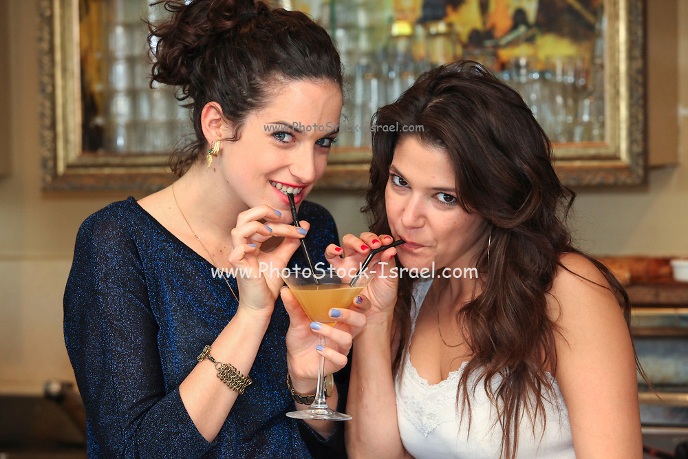 Two young woman share a cocktail