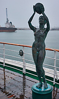 Bronze nude statue holding a bowl on the aft deck of the MV World Odyssey docked at the cruise ship terminal in Ensenada, Mexico.  Image taken with a Nikon N1 V3 camera and 10-30 mm lens (ISO 200, 15 mm, f/4.2, 1/320 sec).
