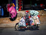 This Vietnamese lady is on a delivery run on her motorbike. So many different items are transported for delivery this way.
