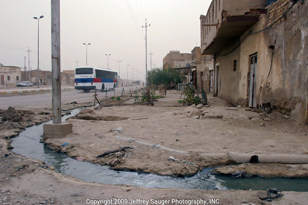 Crude gutters flow with raw sewage in the modernized center of the village Suq ash Shuyukh, about 20 miles southeast of Nasiriyah, Iraq, Wednesday, July 30, 2003.  ..Since the 1991 uprising against Saddam Hussein in Shiite dominated Southern Iraq, people of this area have suffered greatly through his methods of disrupting daily life. For example, modernization came to a hault as money was diverted to Baath Party strongholds. Check points on on every other corner made it nearly impossible to go to work, the doctor, or visit family. Teachers made $5 U.S. per month and had to spend almost all of their salary for taxis in order to go to work...He tried to kill the people by cutting off the rivers that village survival depends on. Dams and canals dirverted the fresh water from flowing into the swamps by way of tributaries. In effect, without fresh water flowing in, the people started poisoning the water supply themselves by using it to wash and clean. Their primitive sewers still flow freely into the same waters that animals use and that feed their rice fields.