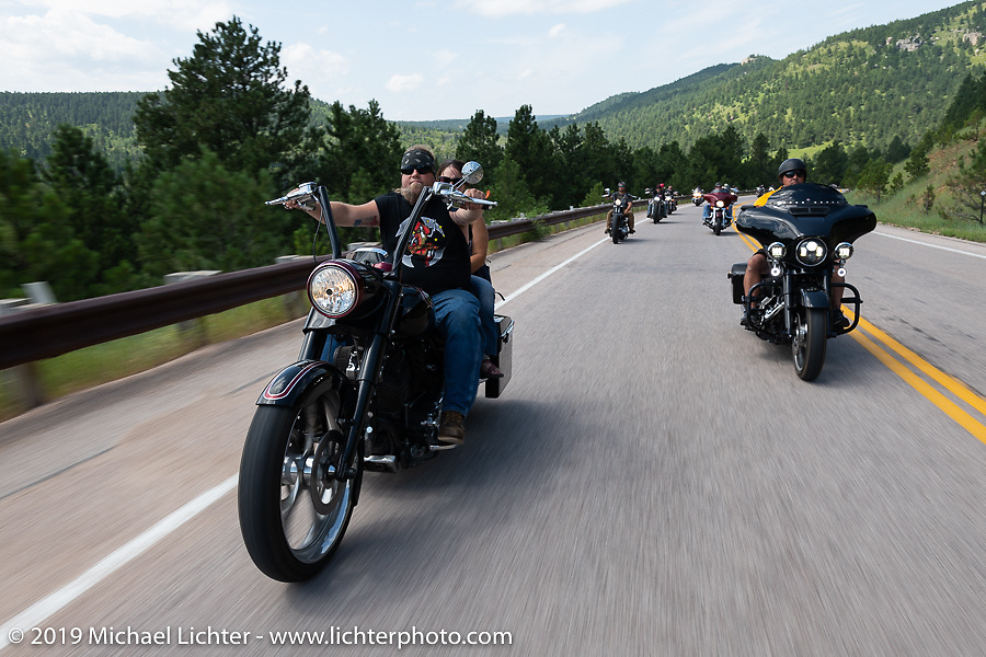 Siouxicide Choppers' Dana Menefee and Nicole ride his bagger on the Cycle Source Ride up Vanocker Canyon to Nemo during the Sturgis Black Hills Motorcycle Rally. SD, USA. Wednesday, August 7, 2019. Photography ©2019 Michael Lichter.