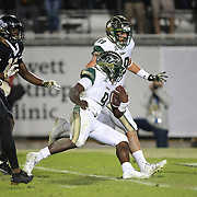 South Florida Bulls quarterback Quinton Flowers (9) runs the ball in for a touchdown during a NCAA football game between the University of South Florida Bulls and the UCF Knights at Spectrum Stadium on Friday, November 24, 2017 in Orlando, Florida. (Alex Menendez via AP)