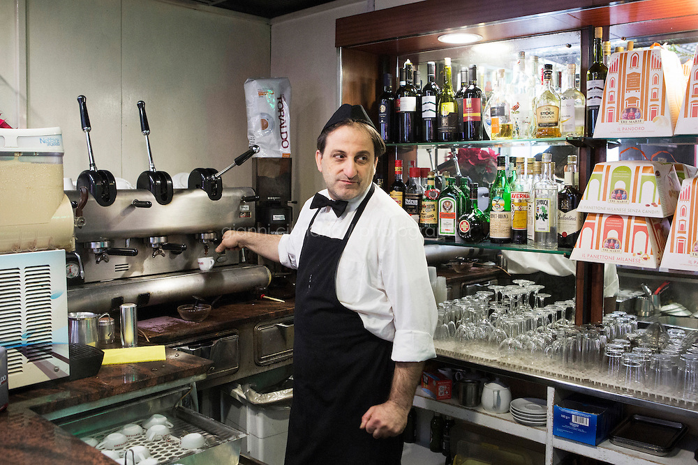 """NAPLES, ITALY - 12 DECEMBER 2014: Ciro Pipolo, a 45 years old barista, prepares an espresso coffee at Bar Settebello, a cafe that is part of the """"Rete del Caffè Sospeso"""" (Suspended Coffee Network) in Naples, Italy, on December 12th 2014.<br /> <br /> A caffè sospeso,or suspended coffee, is a cup of coffee paid for in advance as an anonymous act of charity. The tradition began in the working-class cafés of Naples, where someone would order a sospeso, paying the price of two coffees but receiving and consuming only one. A poor person enquiring later whether there was a sospeso available would then be served a coffee for free."""