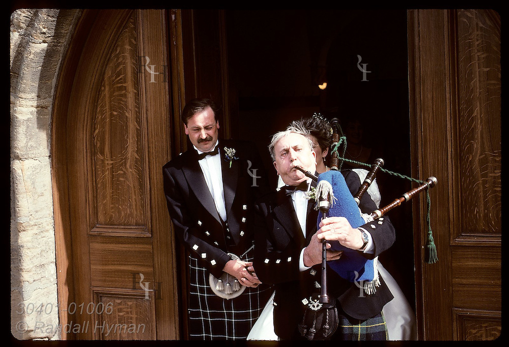 Bagpiper blows mightily as he plays for bride and groom who exit church after wedding; Anstruther Scotland