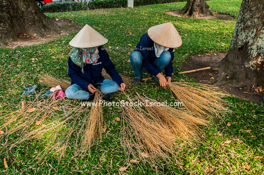 Gardeners make brooms for cleaning a park. Ho Chi Minh City (Saigon), Vietnam