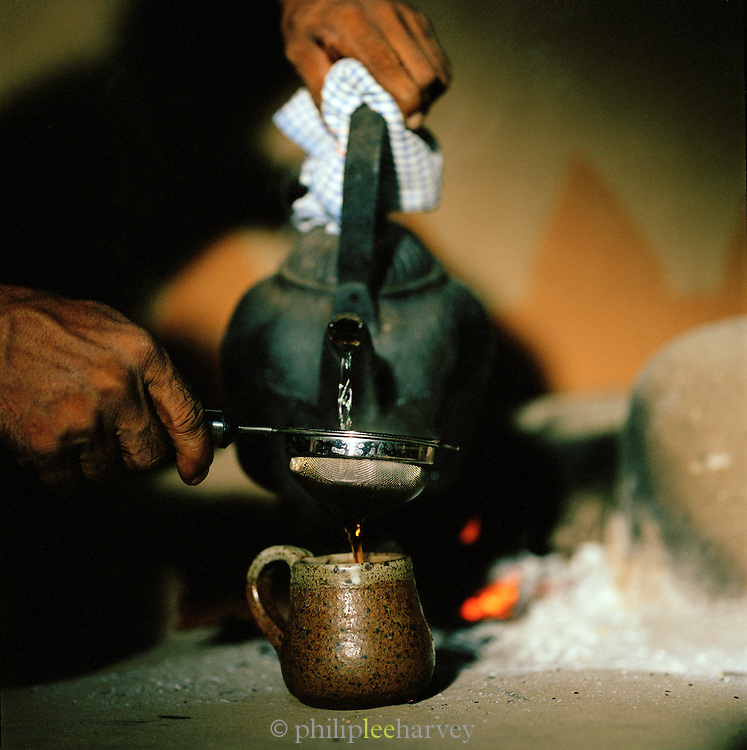 A man serving tea in the traditional village of Ulpotha, Sri Lanka