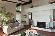 Interior; living room of a rustic house; divan and fireplace