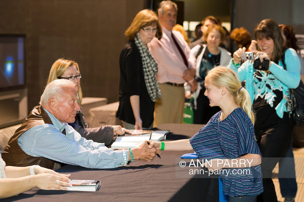 """May 11, 2013 - Garden City, New York U.S. - Astronaut BUZZ ALDRIN, the second person to walk on the moon, shakes the hand of a young girl at the book signing for his new books """"Mission to Mars"""" and the illustrated history of space exploration """"Look to the Stars.""""  After Aldrin, the NASA astronaut engineer of Apollo 11 in 1969, gave a Sold Out lecture, people who bought his books at the museum book store could attend the book signing at the LEM room of the Cradle of Aviation Museum."""