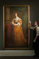 """© Licensed to London News Pictures. 04/12/2015. London, UK. A technician presents """"Portrait of Queen Henrietta Maria"""" by Sir Anthony Van Dyck (est. £1.5-2.0 million) ahead of Sotheby's London evening sale of Old Master and British paintings on 9th December 2015.  Photo credit : Stephen Chung/LNP"""