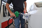 Petrol Station man refuels car with unleaded petrol