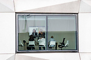 Seen through the window of a corporate office workplace, staff participate in a Zoom meeting in the City of London, the capitals financial district, on 21st September 2021, in London, England. Post-Covid pandemic, City workers are returning to their office desks in greater numbers but many still prefer to work from home for at least 1-2 days a week.