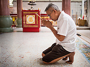 """26 AUGUST 2013 - BANGKOK, THAILAND: A man prays at the Poh Teck Tung Foundation during Hungry Ghost Month in Bangkok. Poh Teck Tung operates hospitals and schools and provides assistance to the poor in Thailand. The seventh lunar month (August - September in 2013) is when the Chinese community believes that hell's gate will open to allow spirits to roam freely in the human world for a month. Many households and temples will hold prayer ceremonies throughout the month-long Hungry Ghost Festival (Phor Thor) to appease the spirits. During the festival, believers will also worship the Tai Su Yeah (King of Hades) in the form of paper effigies which will be """"sent back"""" to hell after the effigies are burnt.     PHOTO BY JACK KURTZ"""