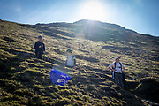 Three children stop and have a break while walking up a steep path on Helvellyn Mountain, Lake District, Cumbria, UK. Helvellyn is the third-highest point in England and is located in the beautiful Lake District National Park and part of the Eastern Fells.