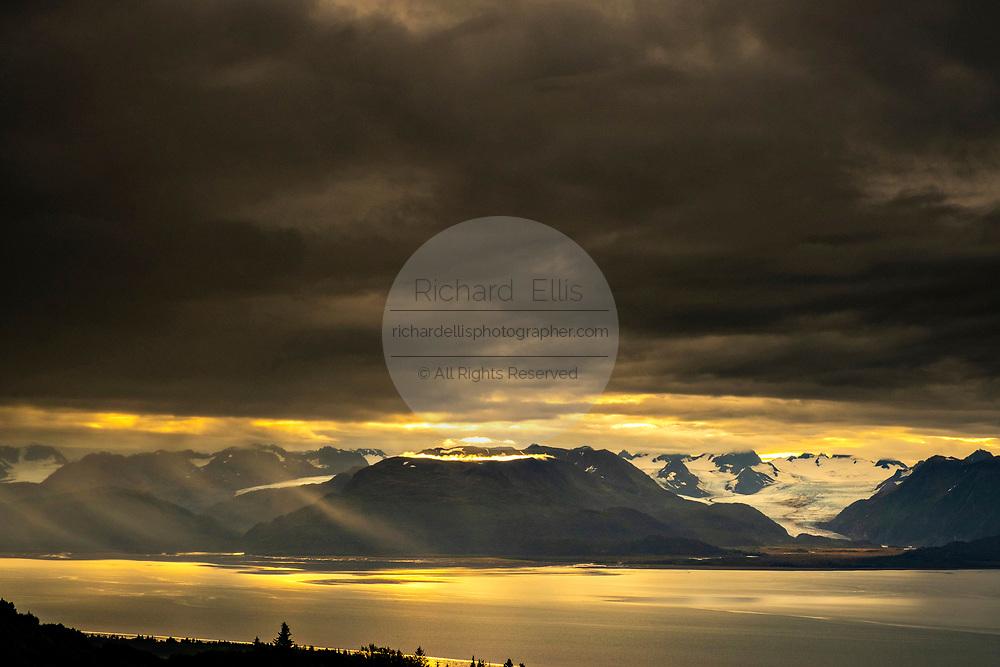Storm clouds part at sunset over Grewingk Glacier along the Kachemak Bay State Park from Homer, Alaska.