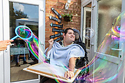 Support worker with service user blowing bubbles.<br /> Client  - Allerton, an integrated social care, housing, and development company.
