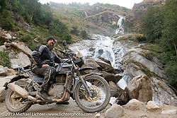 Led Sled's Pat Patterson on his Royal Enfield Himalayan at a roadside waterfall on the Motorcycle Sherpa's Ride to the Heavens motorcycle adventure in the Himalayas of Nepal. On the fifth day of riding, we went from Muktinath to Tatopani. Friday, November 8, 2019. Photography ©2019 Michael Lichter.