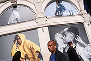 Londoners walk beneath the diverse ethnicities of models outside the Piccadilly Circus branch of clothing retailer, GAP, on 14th October, 2021, in Westminster, London, England.