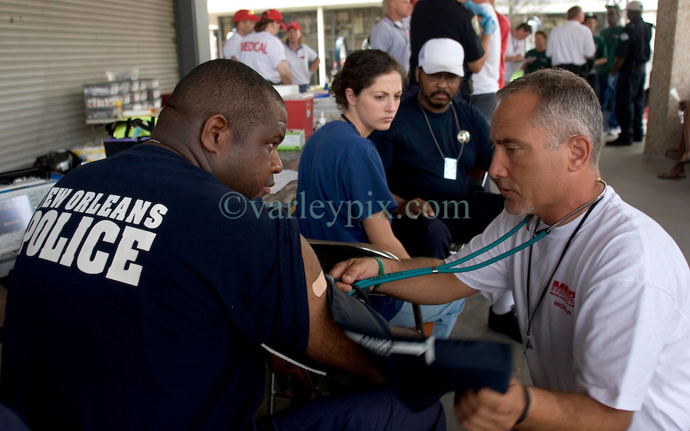 10 Sept 2005. New Orleans, Louisiana.  Hurricane Katrina aftermath.<br /> NOPD officer Taj Magee of the 7th district who fell into the fetid flood waters has his health monitored by Dr David Taylor of the Mobile Medical Response team at the bottom of Canal Street. Officer Magee complained of multiple serious symptoms after his immersion in the water.<br /> Photo; ©Charlie Varley/varleypix.com