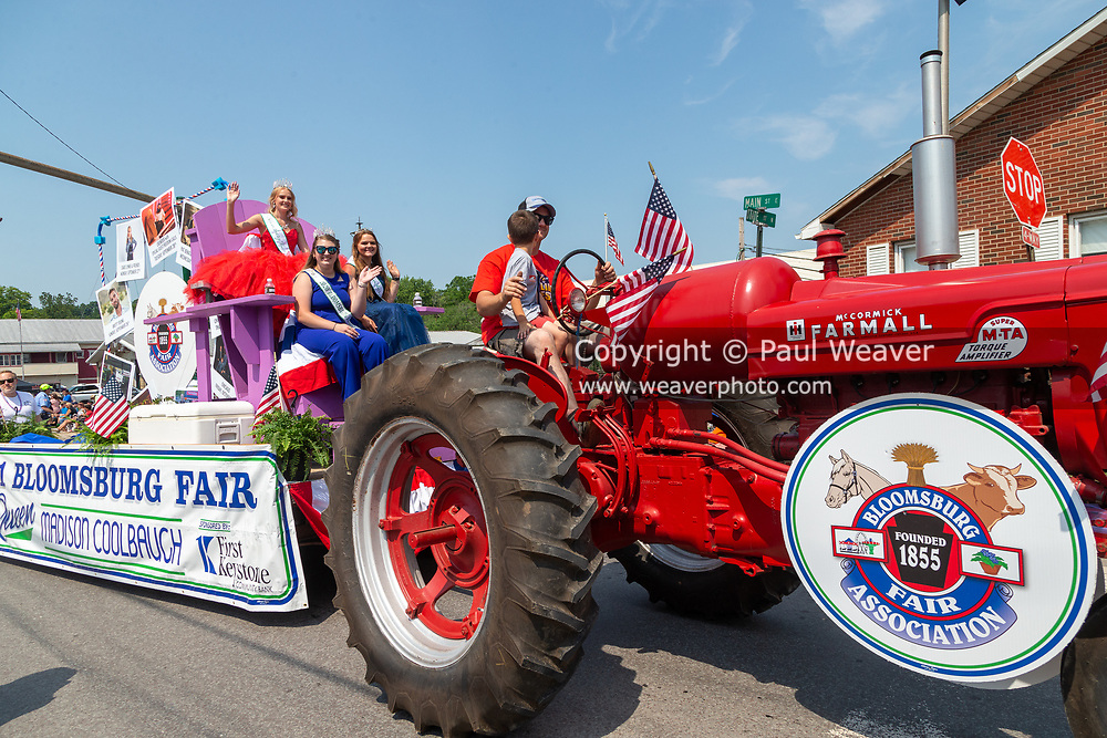 The 2021 Bloomsburg Fair Queen Madison Coolbaugh waves from a float pulled by a farm tractor in the Independence Day parade in Millville, Pennsylvania on July 5, 2021.