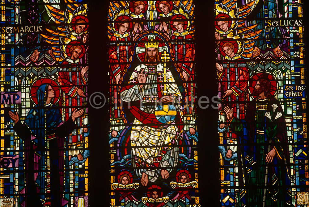 A stained glass depiction of a Christian artwork showing God or Jesus surrounded by angels and accompanied by apostles and/or saints in a London church.