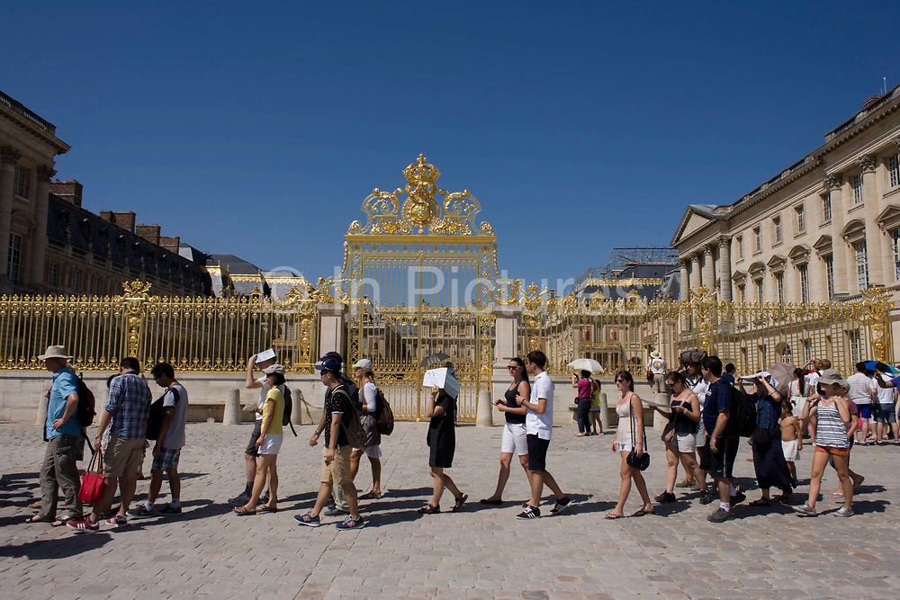Tourists queue to gain entrance below the golden gates of  the Palace of Versaille, near Paris. A total of 100,000 gold leaves were crafted into the shapes of fleur de lys, crowns, masks of Apollo, cornucopias and the crossed capital Ls representing the Sun King. Private donors contributed £4 million to rebuild the 15-ton work, and a plethora of historians and top craftsmen – sculptors, gilders, wrought iron craftsmen and ornament makers – were drafted in to ensure an exact replica of the original built by Jules Hardouin-Mansart in the 1680s.