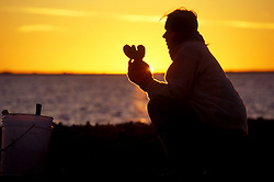 Stock photo of the silhouette of a woman holding an oyster at sunset in Galveston Texas