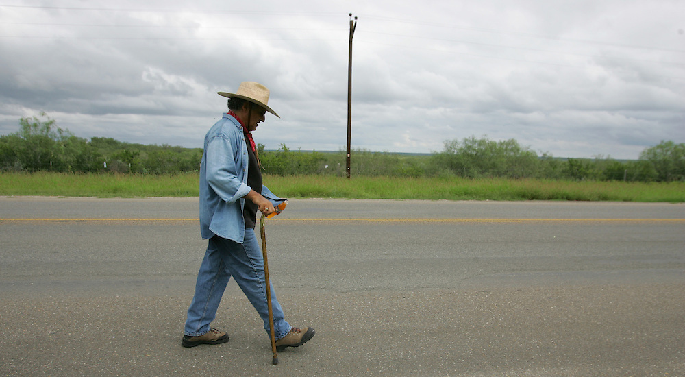 """Jay Johnson Castro walks down Highway 83 outside of Roma, with blisters sending stabbing waves of pain into his feet with every step. """"I just gotta walk... it's the biggest accomplishment just to walk."""" Jay says"""