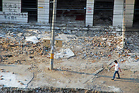 China, Beijing, Chaoyang, San Jian Fang, 2008. A resident walks by the ruins of Chaoyang Street businesses east of Beijing International Studies University. Many will never be rebuilt.