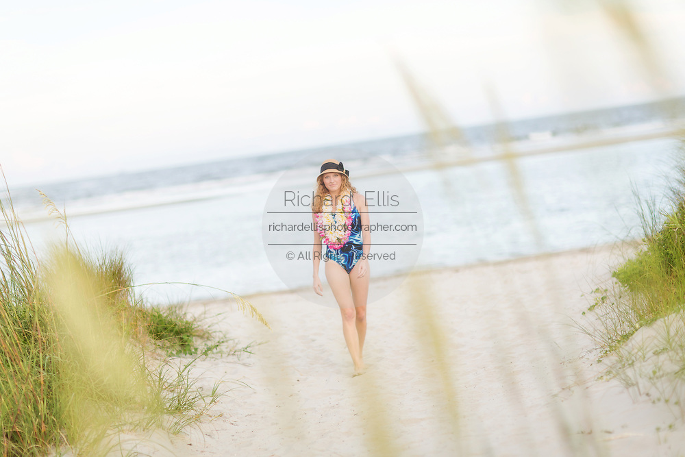 Beautiful curly red head young white woman walking on beach