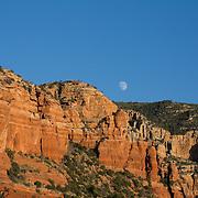 The moon rises over red rocks in Sedona, Arizona.