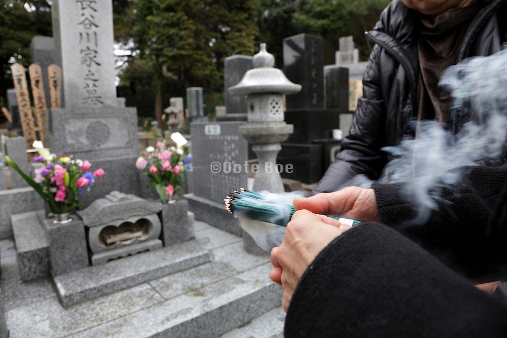 tending to a family memorial grave Japan