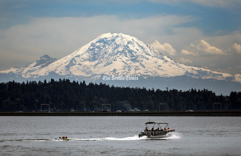 Mount Rainier looms in the background as a pontoon boat drags some children on Lake Washington. (Steve Ringman / The Seattle Times)
