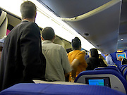 passengers waiting in the aisle to leave the airplane