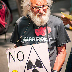 A protestor carries a homemade sign against nuclear energy.