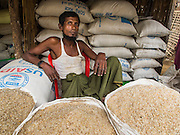 07 NOVEMBER 2014 - SITTWE, RAKHINE, MYANMAR: A Rohingya Muslim man sells rice in an IDP camp for the Rohingya near Sittwe. After sectarian violence devastated Rohingya communities and left hundreds of Rohingya dead in 2012, the government of Myanmar forced more than 140,000 Rohingya Muslims who used to live in and around Sittwe, Myanmar, into squalid Internal Displaced Persons camps. The government says the Rohingya are not Burmese citizens, that they are illegal immigrants from Bangladesh. The Bangladesh government says the Rohingya are Burmese and the Rohingya insist that they have lived in Burma for generations. The camps are about 20 minutes from Sittwe but the Rohingya who live in the camps are not allowed to leave without government permission. They are not allowed to work outside the camps, they are not allowed to go to Sittwe to use the hospital, go to school or do business. The camps have no electricity. Water is delivered through community wells. There are small schools funded by NOGs in the camps and a few private clinics but medical care is costly and not reliable.   PHOTO BY JACK KURTZ