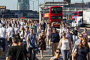 Crowds of commuters walk to work across London Bridge in London, England on August 03, 2018 during hot sunny weather as the heatwave continues in the capital and across Europe.
