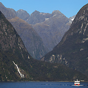 A tourist boat passes Lady Bowen Falls on Milford Sound. Milford Sound (Piopiotahi in Ma¯ori) is a fjord in the south west of New Zealand's South Island, within Fiordland National Park and the Te Wahipounamu World Heritage site. It has been judged the world's top travel destination and is acclaimed as New Zealand's most famous tourist destination..Milford Sound runs 15 kilometres inland from the Tasman Sea at Dale Point - the mouth of the fiord - and is surrounded by sheer rock faces that rise 1,200metres (3,900ft) or more on either side. Among the peaks are The Elephant at 1,517metres (4,977ft), said to resemble an elephant's head and The Lion, 1,302metres (4,272ft), in the shape of a crouching lion. Lush rain forests cling precariously to these cliffs, while seals, penguins, and dolphins frequent the waters and whales can be seen sometimes..Milford Sound sports two permanent waterfalls all year round, Lady Bowen Falls and Stirling Falls. After heavy rain many hundreds of temporary waterfalls can be seen running down the steep sided rock faces. .The beauty of this landscape draws thousands of visitors each day, with between 550,000 and 1 million visitors in total per year. This makes the sound one of New Zealand's most-visited tourist spots, and also the most famous New Zealand tourist destination.  Milford Sound, New Zealand. 29th April 2011. Photo Tim Clayton