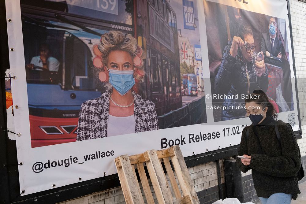 A woman wearting a face covering walks past a banner promoting the new book about bus travel during the Coronavirus pandemic by Glaswegian street photographer, Dougie Wallace (aka Glasweegee), in Shoreditch, on 24th February 2021, in London, England.