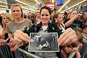 Emilie Creswell of Salt Lake City, center, shows off a photo of the Twilight cast as she waits with other fans for the arrival of Twilight star Rachelle Lefevre who plays the character Victoria, at the Walmart store in Riverton, Utah during the midnight DVD movie release event March 20, 2009. (AP Photo/Colin Braley)