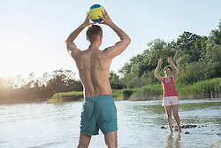 Mature couple playing volleyball at the lake, Bavaria, Germany