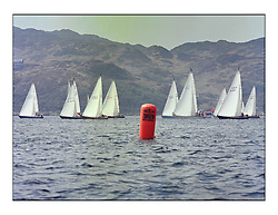 The Clyde Cruising Club's 1977 Tomatin Trophy the first Scottish Series held at Tarbert Loch Fyne.  An overnight race from Gourock to Campbeltown then on to Olympic Triangles in Loch Fyne. ..Fleet Start with branded mark in foreground. The IOR style of masthead genoas power the fleet through the waters of Loch Fyne..