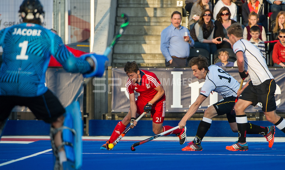 Great Britain's Tim Whiteman drives into the circle past Jonas Gomoll of Germany. Great Britain v Germany, Lee Valley Hockey & Tennis Centre, London, UK on 14 April 2015. Photo: Simon Parker
