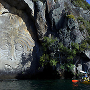 Kayakers visit the Maori rock carvings at Mine Bay, Lake Taupo. ..Master carver Matahi Whakataka-Brightwell carved Ngatoroirangi, his first ever rock carving, onto the cliff face at the southern end of Mine Bay. The Maori rock carvings are over 10 metres high and are only accessible by boat. In the late 1970s master carver Matahi Whakataka-Brightwell came to his mother's land at Lake Taupo.  On a boat trip around the Western Bays he saw the cliffs at Mine Bay and decided to use them as a canvas for his work...Matahi decided to carve a likeness of Ngatoroirangi, a visionary Maori navigator who guided the Tuwharetoa and Te Arawa tribes to the Taupo area over a thousand years ago.  In recognition of the multi-cultural nature of New Zealand, Matahi also carved two smaller figures of Celtic design, which depict the south wind and a mermaid.  The Ngatoroirangi carving took four summers to complete and the carvers took no payment other than donations to cover the cost of the scaffolding.  The carving has become an important cultural attraction for the region. Lake Taupo, New Zealand,, 8th January 2011.  Photo Tim Clayton.
